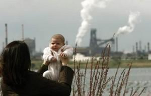 Bambino, sullo sfondo le acciaierie ILVA di Taranto