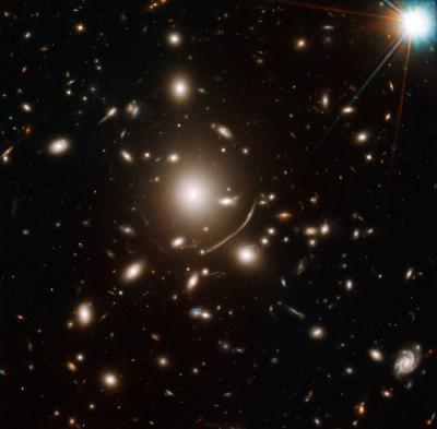 Il gigantesco ammasso di galassie ellittiche nel centro di questa immagine contiene tanta massa di materia oscura che la sua gravità curve di luce. Questo ha permesso la scoperta della galassia più antica mai osservata. Crediti: NASA, ESA, J. Richard (CRAL) and J.-P. Kneib (LAM). Acknowledgement: Marc Postman (STScI)