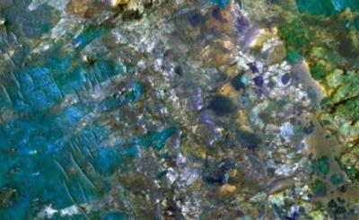 Immagine colorata artificialmente, ripresa da uno strumento a bordo del Mars Reconnaissance Orbiter della NASA, che mostra l'estrema variabilità di rocce del sottosuolo marziano, riportate alla luce da un impatto meteoritico. La dimensione reale è di 1 chilometro. L'esame di queste rocce potrebbe chiarire meglio la possibilità di remote forme di vita. (crediti: NASA / JPL / Università dell'Arizona)