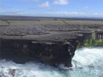 Esempio di massi costieri nelle Isole Aran. Le falesie sono alte circa 20 metri e i massi vengono ammucchiati a 32-42 metri nell'entroterra dal bordo della riva. Da notare le dimensioni delle persone vicino ai massi, del peso di alcune tonnellate gettati a riva durante l'inverno 2013-2014 (crediti: Peter Cox)